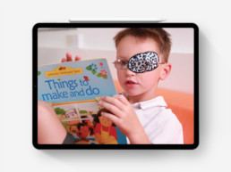 Photograph of child with eye patch reading on iPad Pro
