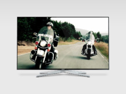 Photograph of two motor bikers riding in the countryside on a Samsung monitor